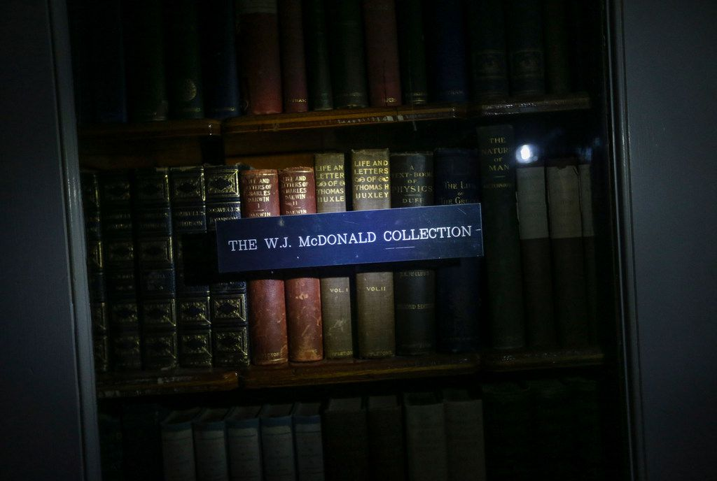 Books from the original W.J. McDonald Collection are illuminated by a flashlight at McDonald Observatory.