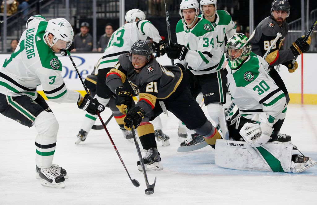 Vegas Golden Knights center Cody Eakin (21) reaches for the puck in front of Dallas Stars goaltender Ben Bishop (30) during the second period of an NHL hockey game Tuesday, Feb. 26, 2019, in Las Vegas. (AP Photo/John Locher)