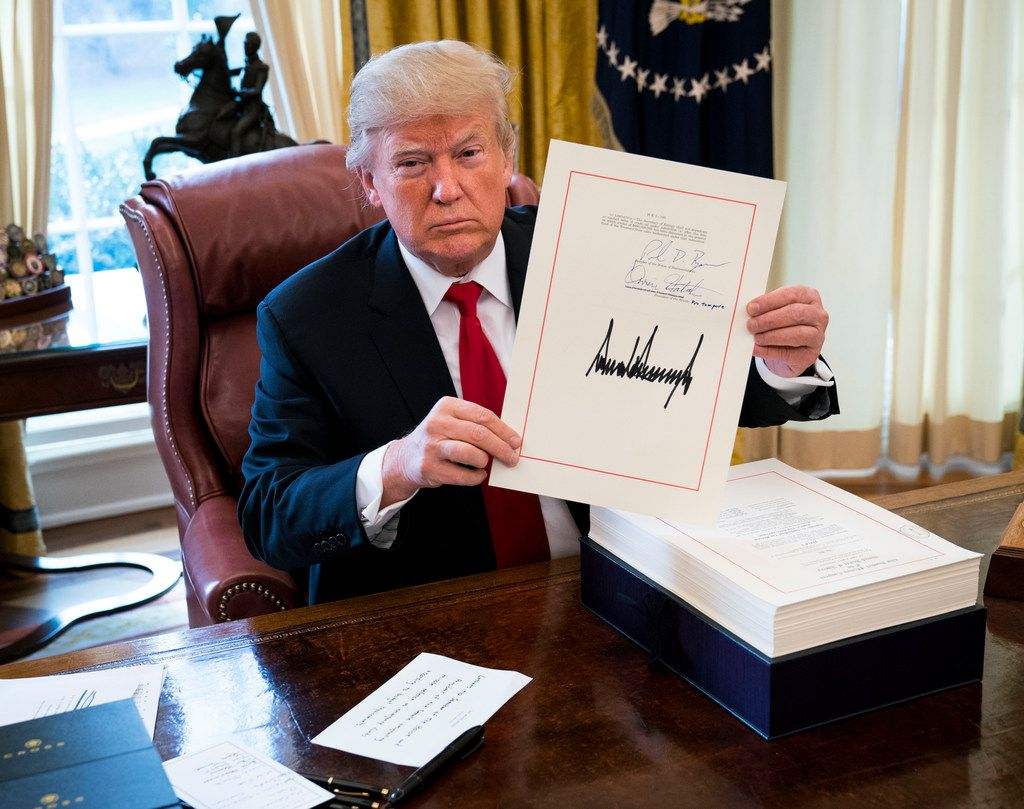 President Donald Trump displays his signature on a sweeping tax bill in the Oval Office of the White House on Dec. 22, 2017.  (Doug Mills/The New York Times)
