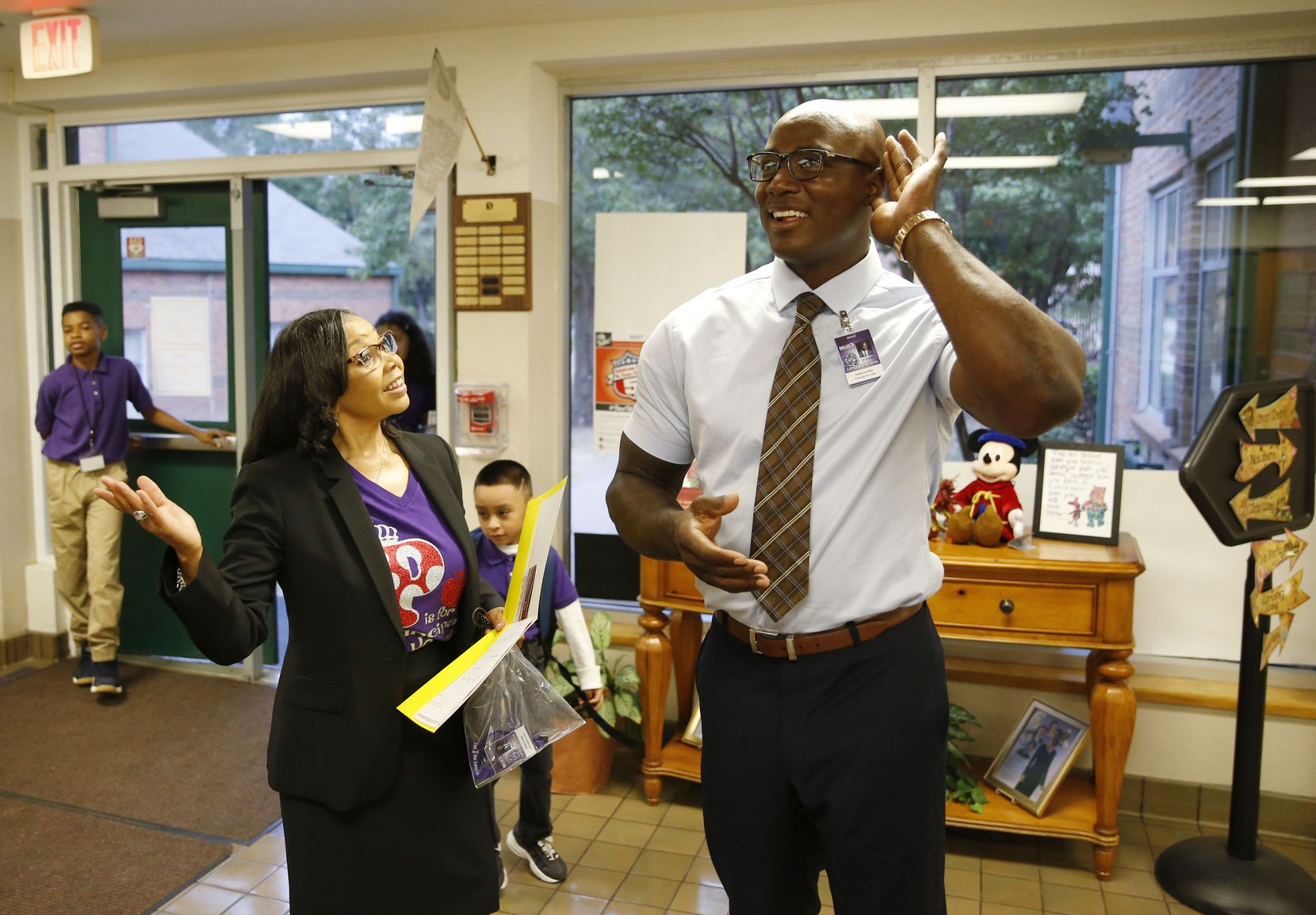 """Ware listens with Starks principal Lynette Howard and students as """"New Day,"""" a gospel song by The Walls Group, plays over the intercom."""