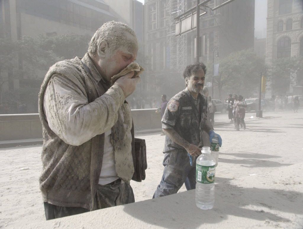 In this Sept. 11, 2001 file photo, a man wipes ash from his face after terrorists flew two airplanes into the World Trade Center towers, causing them to collapse.