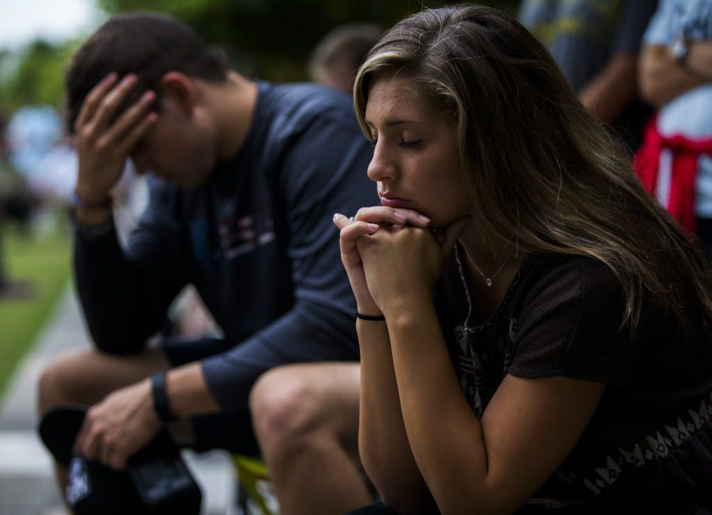 People pray at a service hosted by Watermark Community Church, held at the deck park in downtown Dallas. (Ashley Landis/Staff Photographer)