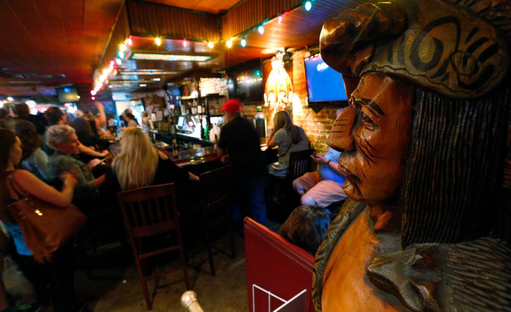The statue of a wooden Indian looks on as the Elbow Room in Dallas nears its last call. (Nathan Hunsinger/The Dallas Morning News)