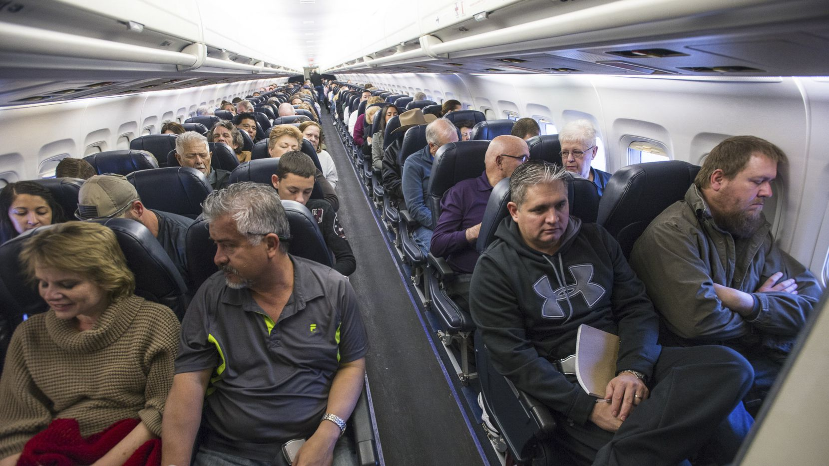 Passengers on a flight in Las Vegas, April 18, 2016. As planes fly at record capacity and new cabin configurations squeeze in ever more passengers, airlines are, intentionally or not, nudging fliers into paying extra to avoid drawing the proverbial short straw of the middle seat. (Joe Giron/The New York Times)