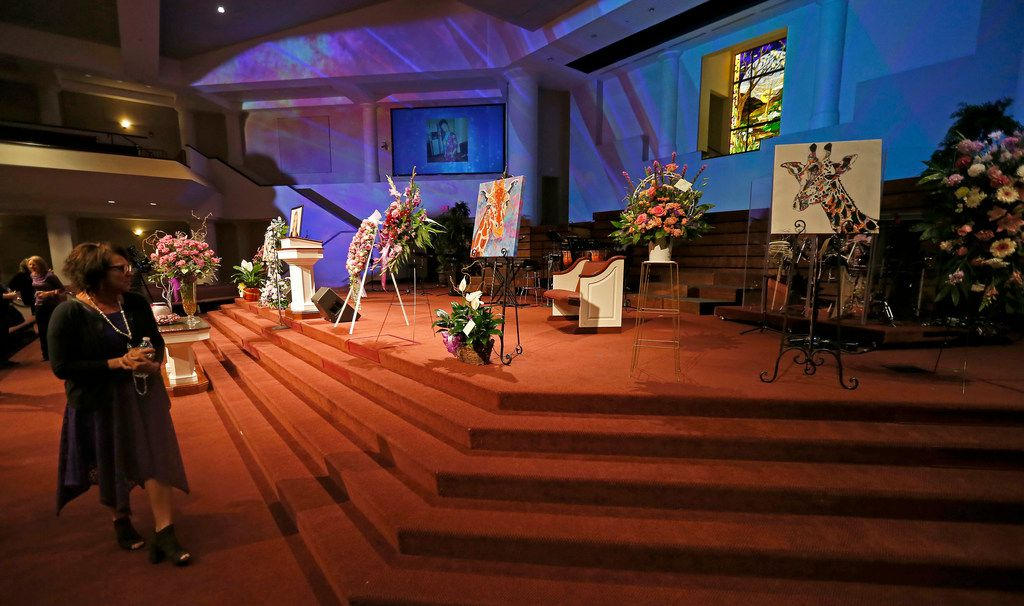 Jonni Hare, mother of kidnap victim Christina Morris, takes a look at images of giraffes in abundance before a memorial service for her daughter at First Baptist Church in Allen, Texas, on Saturday, April 21, 2018.