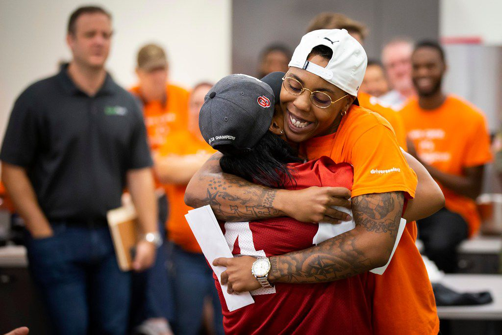 """CiCi Hall (facing) hugs D.C. Cole after nominating her for a """"CARE"""" award during the monthly """"all-tribe"""" kick off meeting at driversselect  Grand Prairie."""