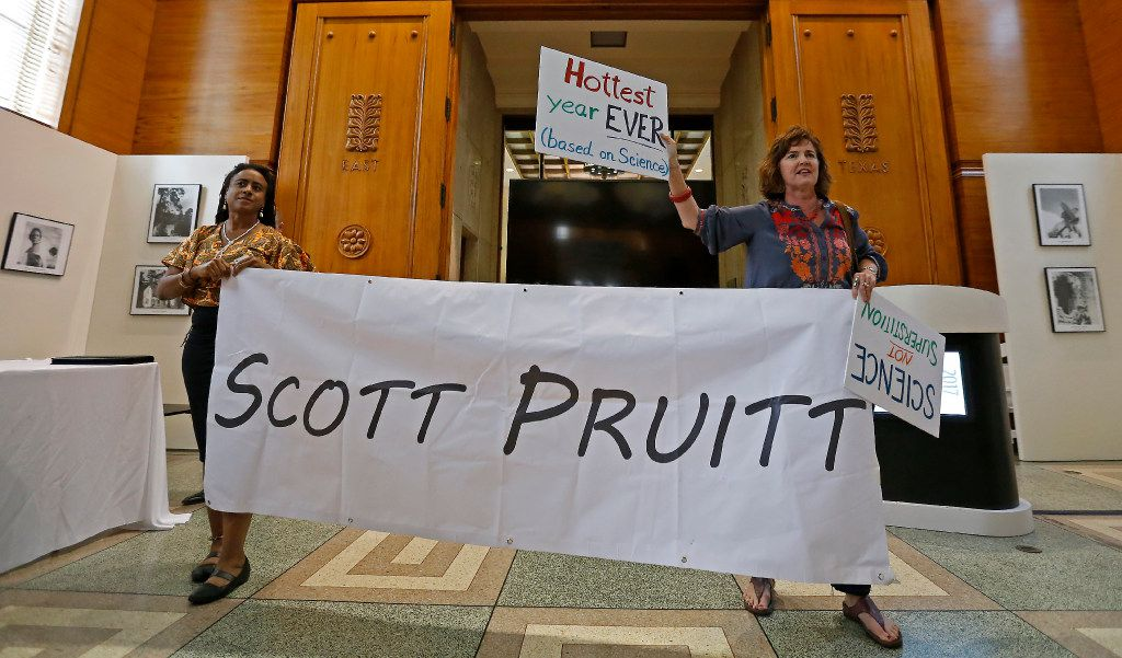Protesters Cherelle Blazer (left) and Danna Miller Pyke hold a banner inside the Hall of State before Environmental Protection Agency Administrator Scott Pruitt speaks at the Celebration of Earth Day at Fair Park.