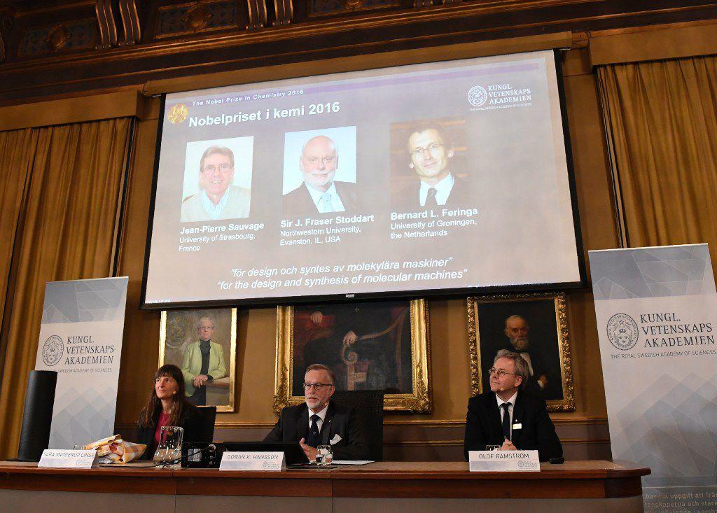 Los ganadores del Premio Nobel de Química (de izquiera a derecha en pantalla) Jean-Pierre Sauvage, J Fraser Stoddart y Bernard L Feringa son anunciados por el comité Nobel en esa rama. (AP)