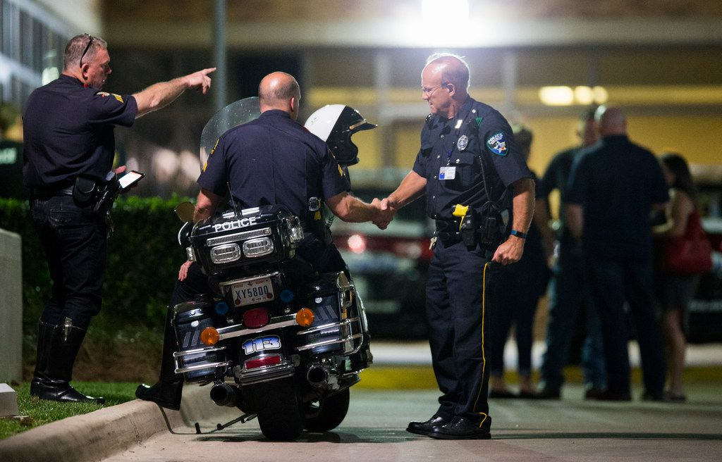 Police officers stand outside the emergency room at Texas Health Presbyterian Hospital Dallas after a man shot two officers outside a Home Depot on Tuesday, April 24, 2018 in Dallas. (Ashley Landis/Staff Photographer)