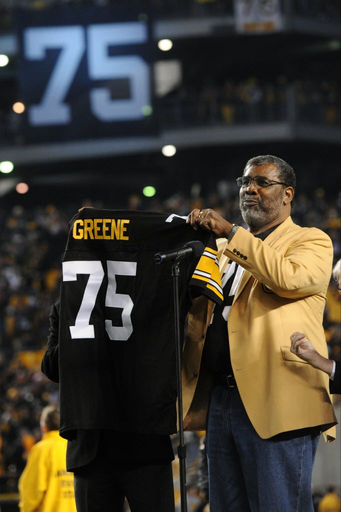 Former Pittsburgh Steelers defensive lineman Joe Greene holds a jersey at a ceremony where the team revealed markers in the rotundas at Heinz Field marking the retirement of his jersey number in 2014. (Don Wright/The Associated Press)