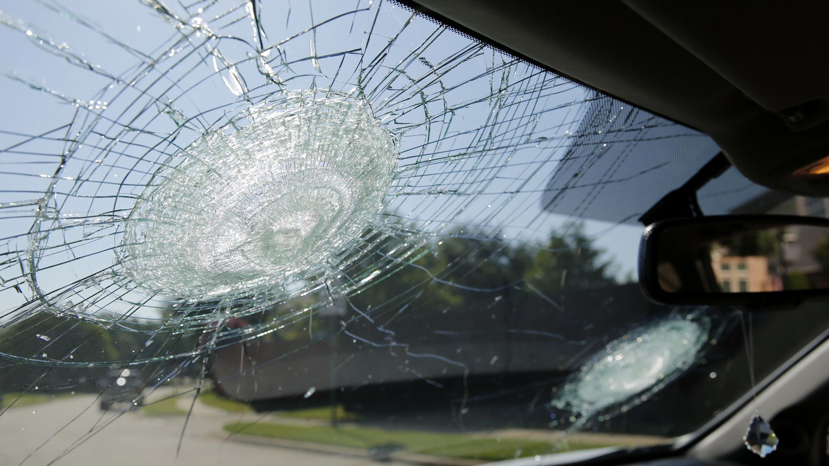 Two large indentations caused by hail in the windshield of a vehicle in Coppell.