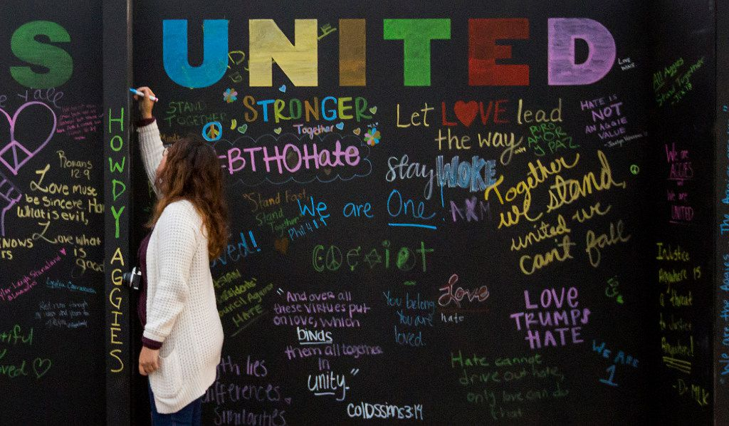 Bailey Wilbanks, a senior from Lubbock, writes on a chalkboard before the Aggies United event.