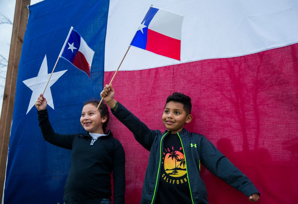 Gianna Bocanegra and Chris Madrid pose for photos with Texas flags at TexFest in downtown Carrollton.