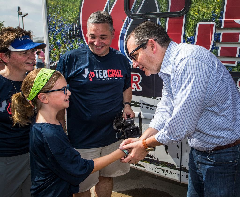 Campbell Steinhagen, 10, of McLendon-Chisholm, Texas, left, shakes the hand of Texas Sen. Ted Cruz, as her parents Michelle, left, and Robert Steinhagen, watch before a Fourth of July parade in Rockwall, Texas on July 4, 2018. Cruz rode in the the annual Independence Day parade.