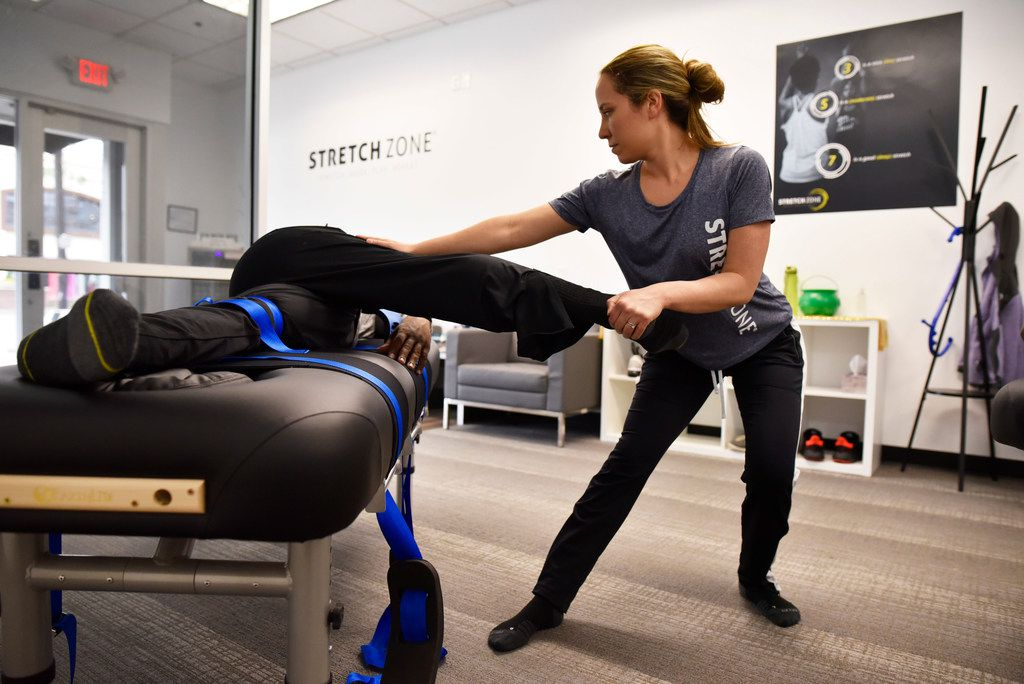 Stretch practitioner Danielle D'Alesio works on client Sergeant Jeff Wilson, of the Dallas County Sheriff Department. Stretching gyms are an interesting, trendy way to stay limber.