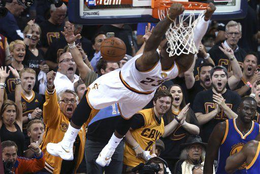 Los espectadores gritan mientras LeBron James, de los Cavaliers de Cleveland, realiza una clavada en el sexto partido de la final de la NBA, ante los Warriors de Golden State, el jueves 16 de junio de 2016 (AP Foto/Ron Schwane)