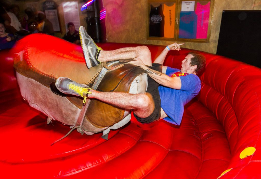Cory Laubscher of Georgetown, Texas, falls off a mechanical bull at The Trophy Club on Sixth Street during SXSW.