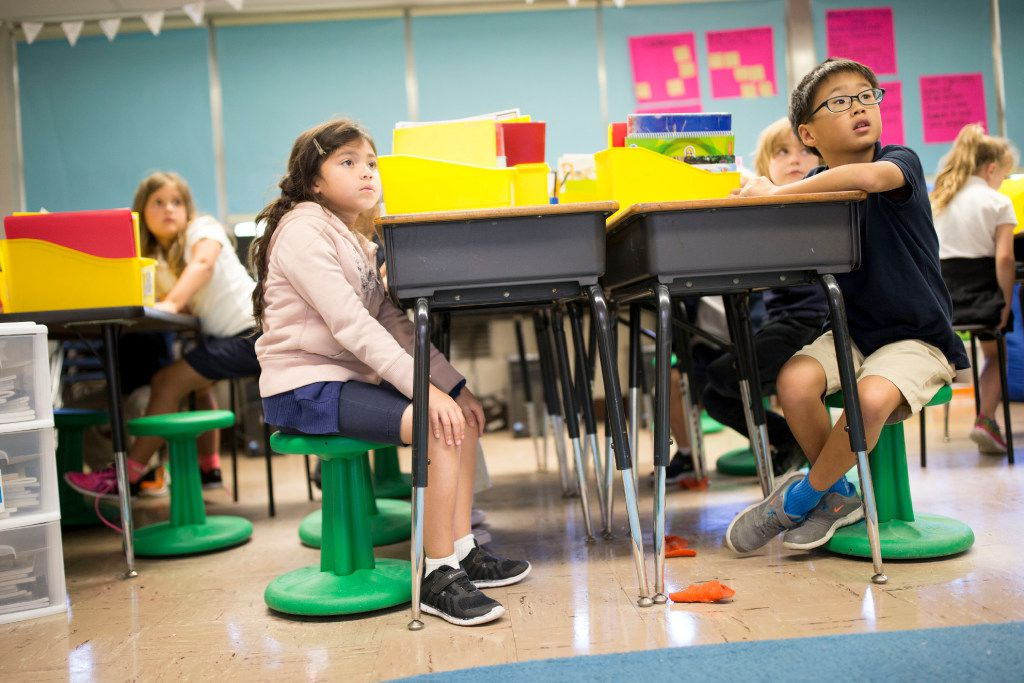 Leia Pena (left), 7, and Daniel Kang, 7 sit on wobble stools donated from Staples though DonorsChoose.org during second-grade reading class at Hexter Elementary. (Ting Shen/Staff Photographer)
