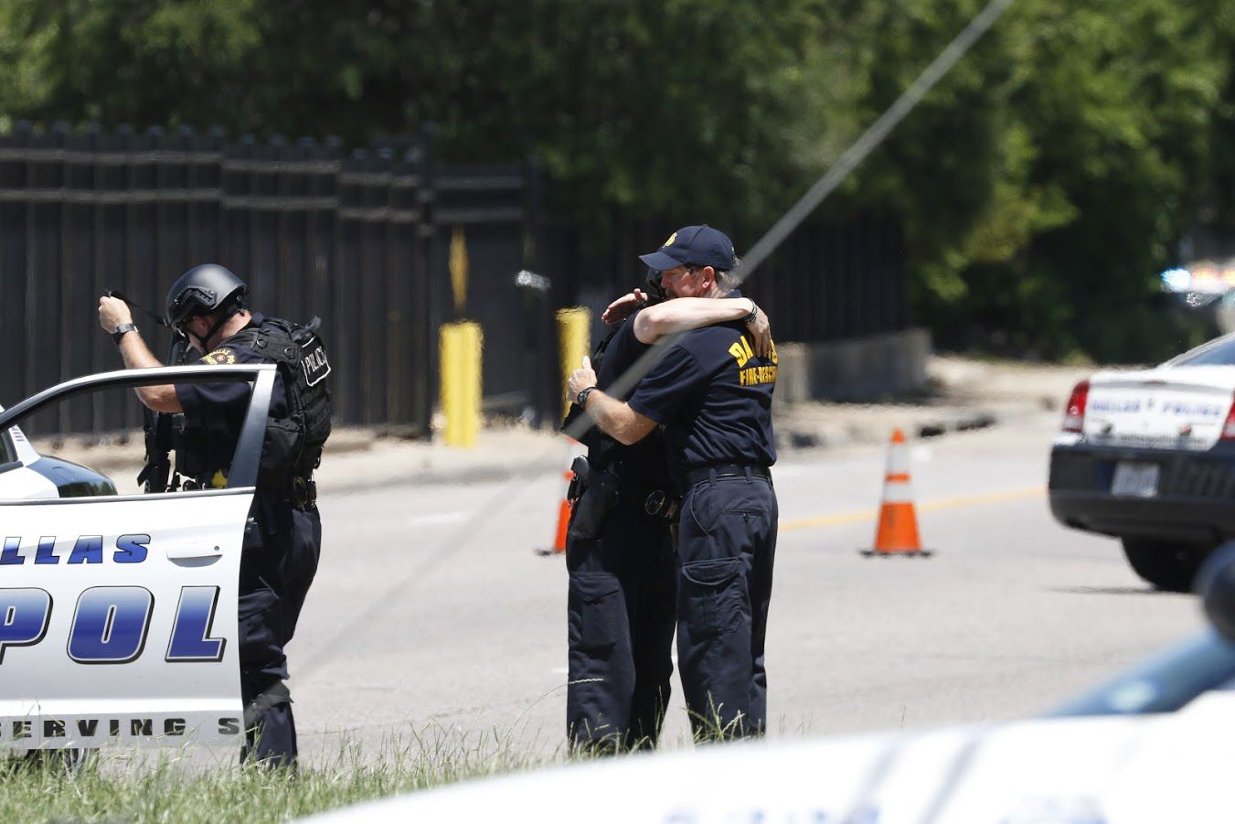 William Bruce (right) embraces son Chase near the scene of Monday's fatal shooting that left two dead and sent paramedic William An to the hospital in critical condition. (Jae S. Lee/The Dallas Morning News)