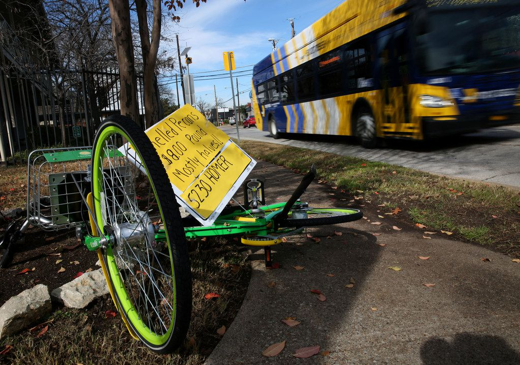 A sign advertising shelled pecans is stuck through an overturned LimeBike on the sidewalk along Henderson Avenue in Dallas on Dec. 21, 2017.
