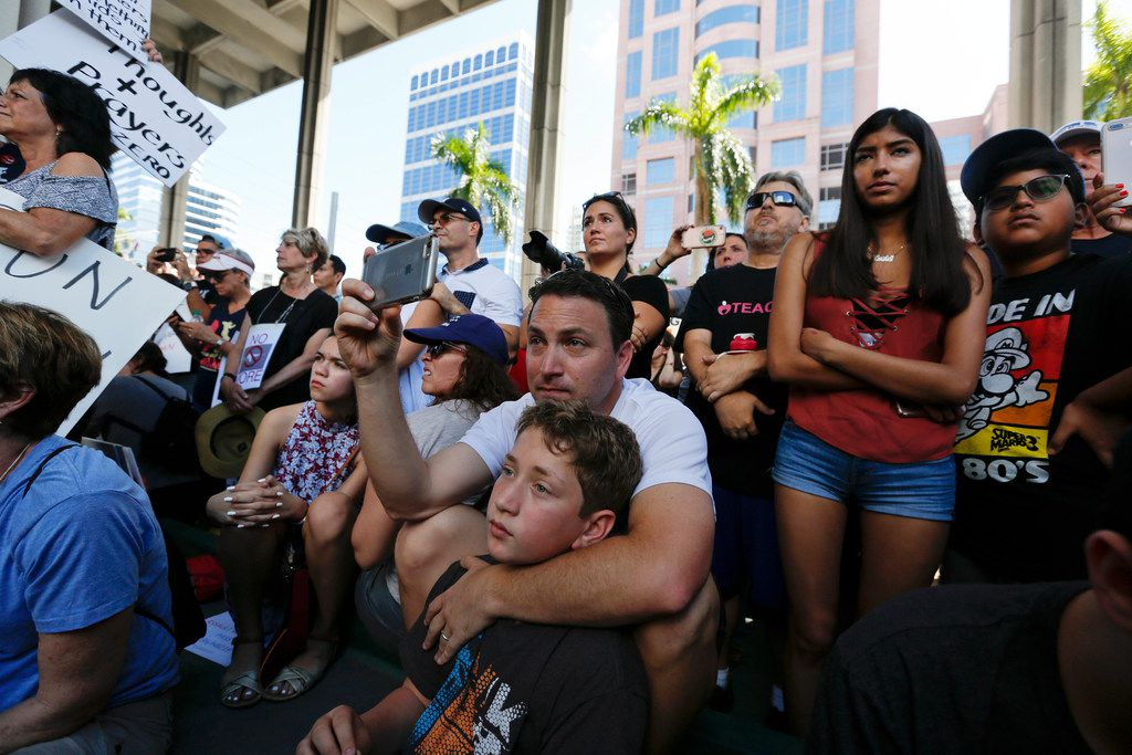 Louis Reinstein, embraces his son, Daniel, 10, during a protest against guns on the steps of the Broward County Federal courthouse in Fort Lauderdale, Fla., on Saturday. Nikolas Cruz, a former student, is charged with killing 17 people at Marjory Stoneman Douglas High School in Parkland, Fla., on Wednesday.