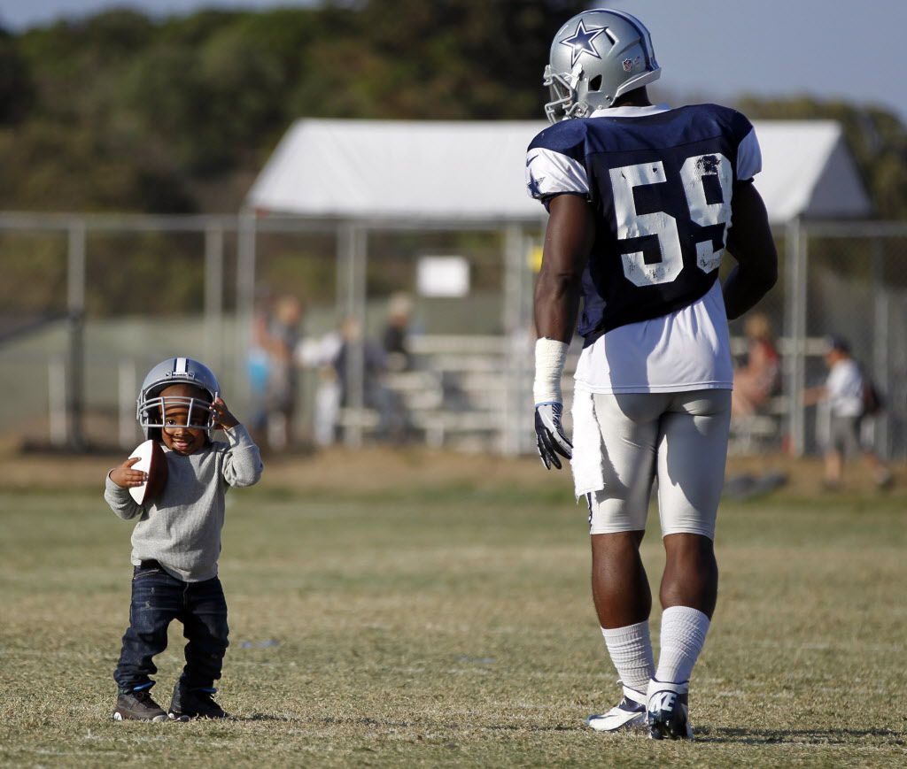 Ernie Sims IV plays with his father Dallas Cowboys inside linebacker Ernie Sims (59) during the afternoon practice at Dallas Cowboys training camp in Oxnard, California on August 1, 2013. (Vernon Bryant/The Dallas Morning News)