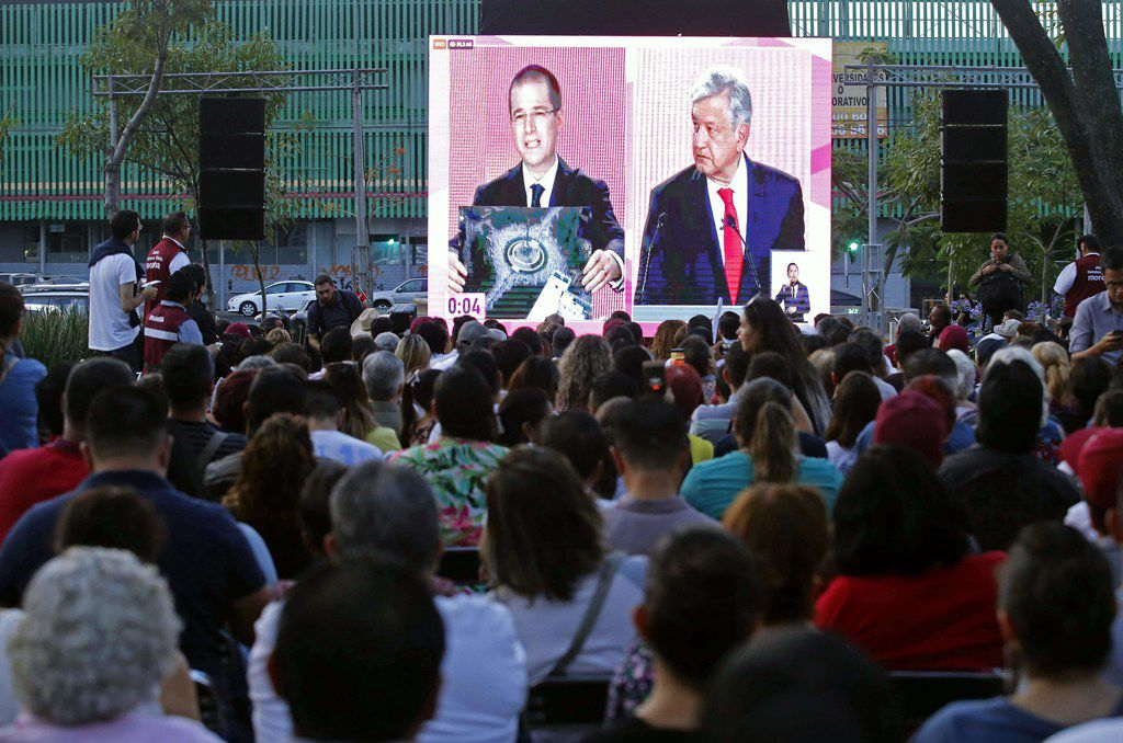 People watch a public television screen showing Mexico's presidential candidate Ricardo Anaya, left, and presidential candidate for the MORENA party, Andres Manuel Lopez Obrador during the coverage of the first presidental debate at Chapultepec Avenue in Guadalajara, Jalisco State, Mexico, on April 22, 2018.