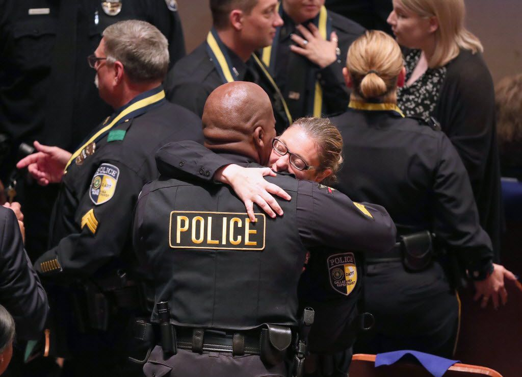 DART officer Misty McBride hugged a fellow officer before a July 12 memorial service honoring five slain police officers. McBride was wounded when Micah Johnson opened fire on officers patrolling a peaceful protest against police shootings.