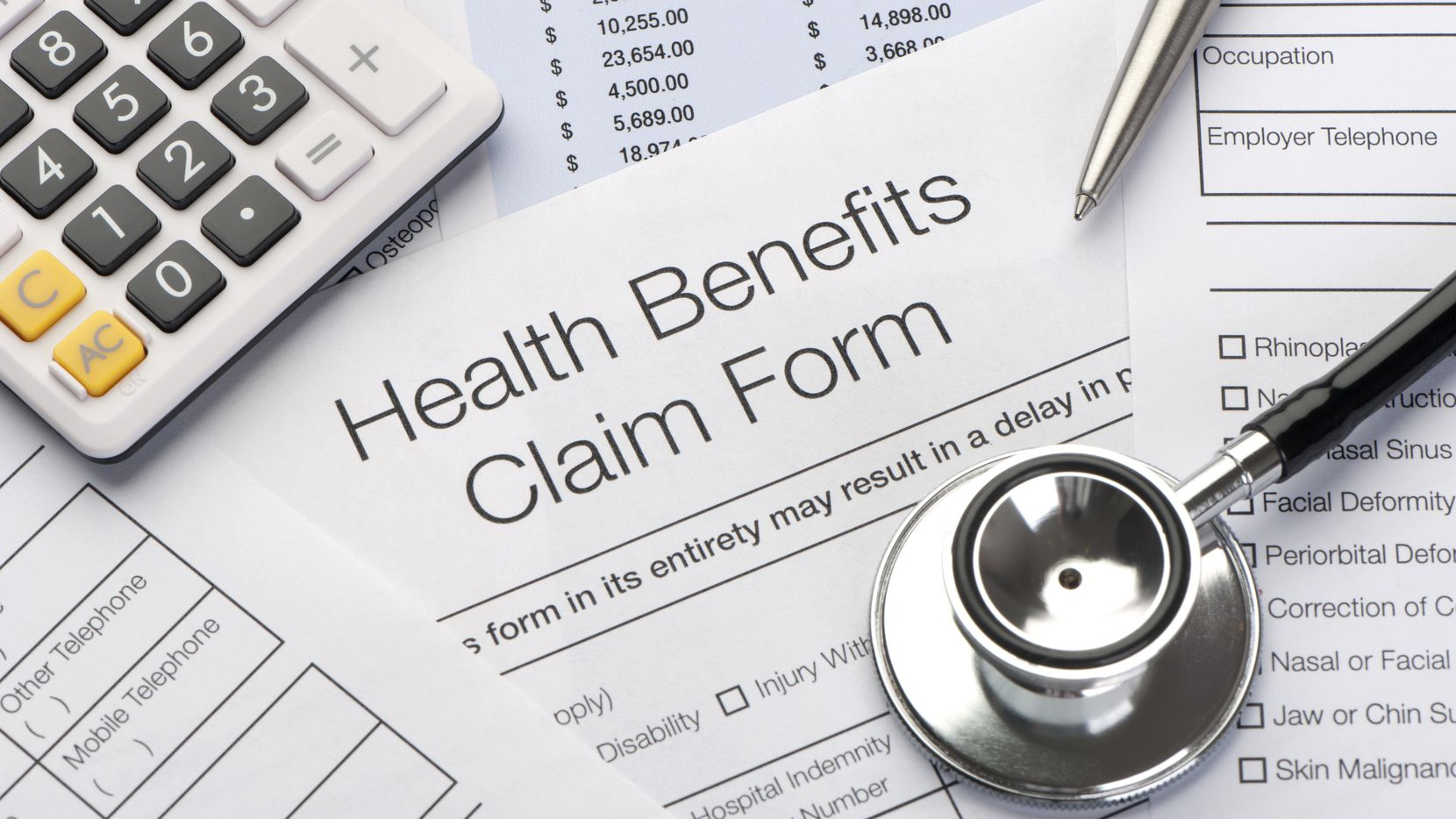 Close up a Health benefits claim form with calculator, pen and stethoscope