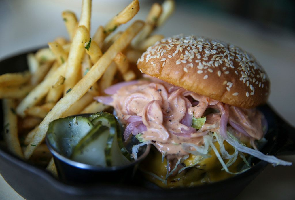 One of the most popular menu items at Punch Bowl Social is the Knockoff Burger, made with two all-beef patties, comeback sauce, lettuce, cheese, pickles, onions on a sesame seed bun. (Get it?)