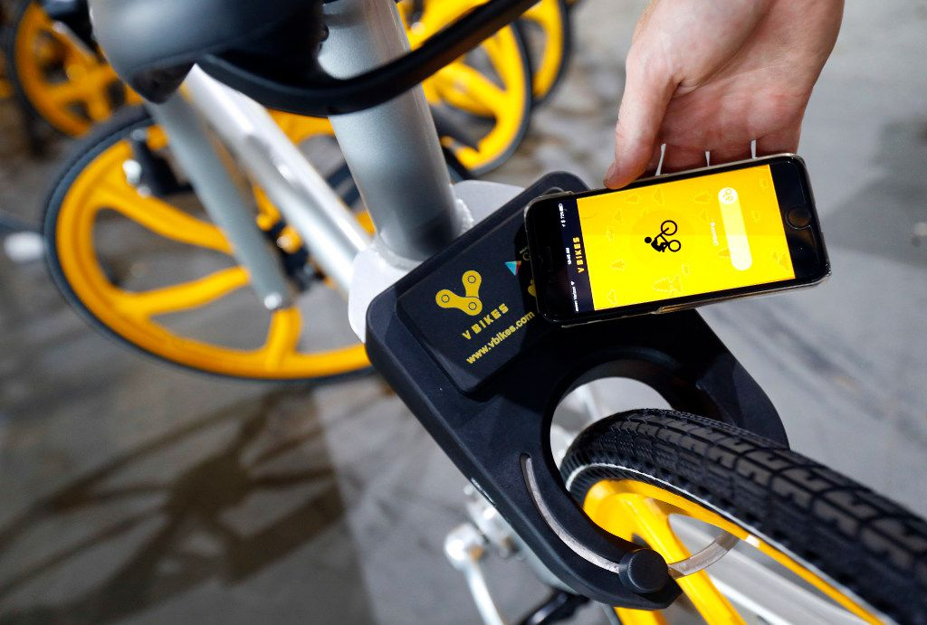 The app on a smartphone is used to unlock a VBike smart lock box on the rear tire of a bicycle.