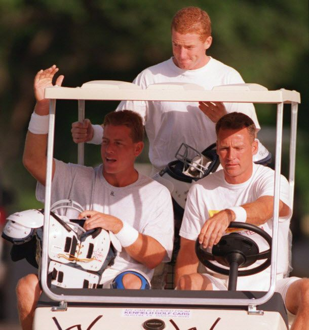 The Dallas Cowboys quarterbacks Troy Aikman (seated-left), Wade Wilson (seated-right) and Jason Garrett (standing) enter the  practice field together in Wilson's golf cart on the opening  morning of 1995 training camp.  FILE PHOTO