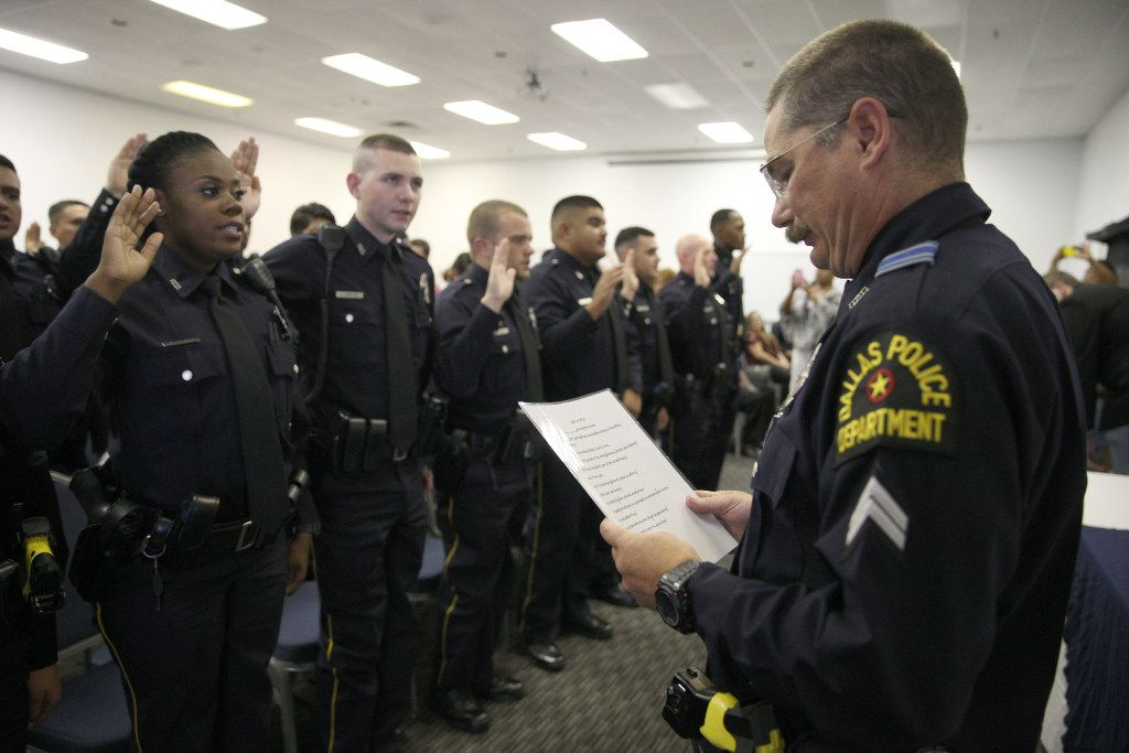 New Dallas police officers take an oath after receiving their badges on Thursday, August 18, 2016 at the Dallas Police Training Academy in Dallas. The class is the first to graduate since Dallas officers were targeted in a shooting on July 7, 2016.