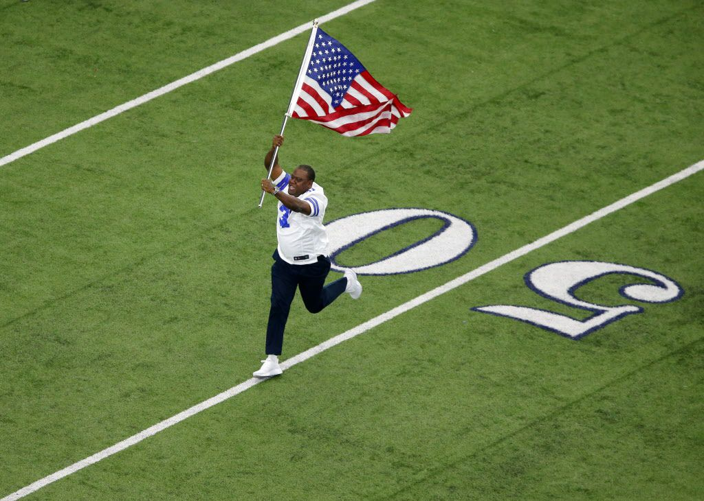 Former Dallas Cowboys player George Teague leads the team onto the field with the U.S. flag at AT&T Stadium in Arlington, Texas, Sunday, September 11, 2016. Teague led the Cowboys onto the field following 9/11, 15 years ago. (Tom Fox/The Dallas Morning News)