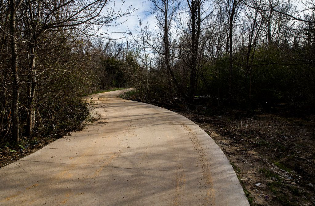 A concrete trail winds through the McCommas Bluff Preserve. I