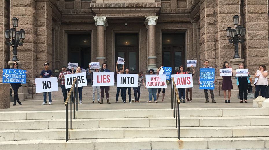 "Protesters with the Texas Freedom Network hold signs outside the Texas Capitol on Thursday morning that read: ""No more lies into anti-abortion laws"""