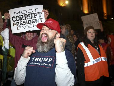 "A Trump supporter chanted ""Trump 2020"" while making his way through crowd of anti-Trump protesters Thursday night, Oct. 10, 2019, in Minneapolis. President Donald Trump held a campaign rally Thursday at the Target Center. (Aaron Lavinsky/Star Tribune via AP)"