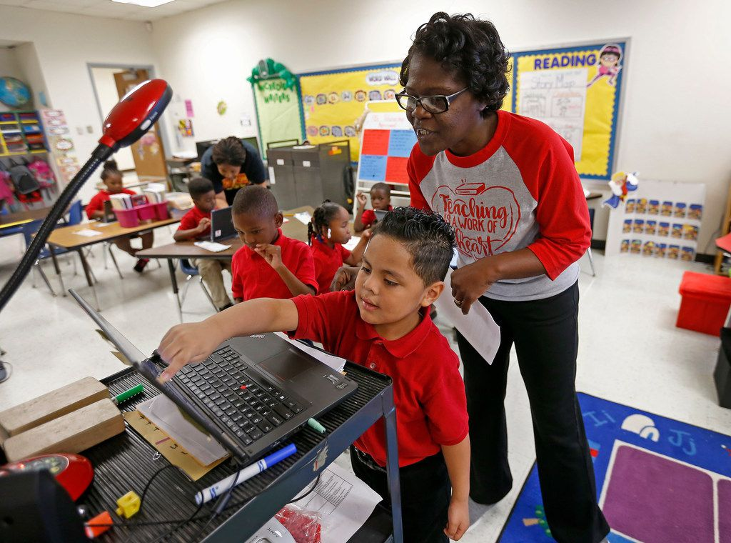Teacher Vondella Rogers (right) helps her kindergarten student Adrian Flores work on lesson during a coding class at Frederick Douglass Elementary in Dallas.