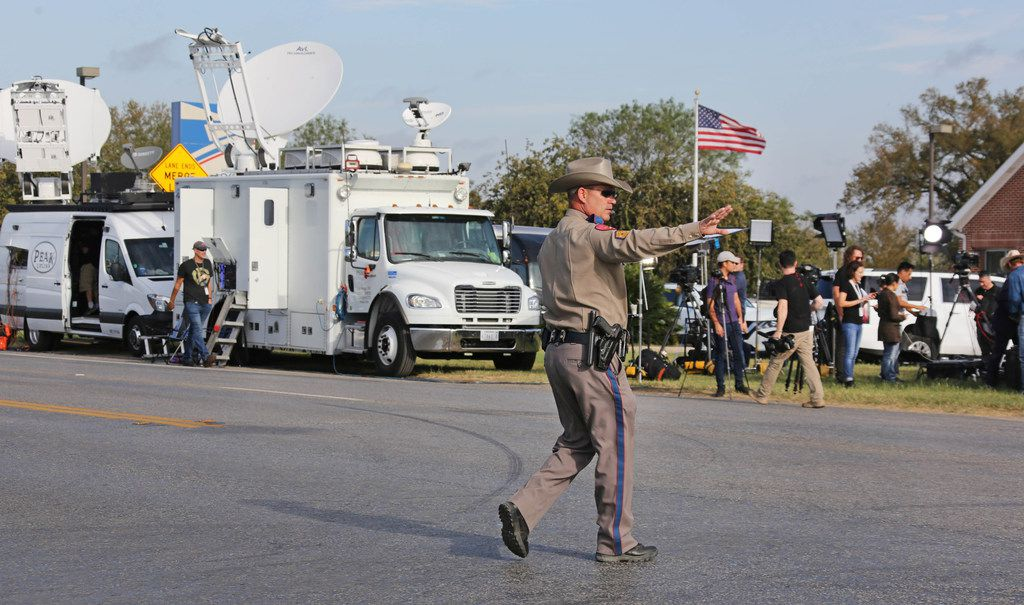 A Texas state trooper directs traffic at the intersection near the First Baptist Church of Sutherland Springs, Texas. At least 26 people died Sunday after a gunman opened fire at a Baptist church in the small town southeast of San Antonio. Photographed on Monday, November 6, 2017. (Louis DeLuca/The Dallas Morning News)