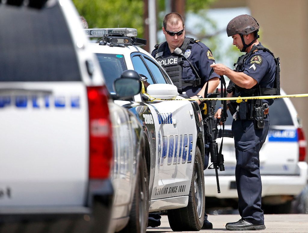 Dallas Police Department officers put their gear in a trunk outside an office building in Lake Highlands near the High Five where police found two people dead inside the office building in Dallas, Monday, April 24, 2017. Crowe (Jae S. Lee/The Dallas Morning News)