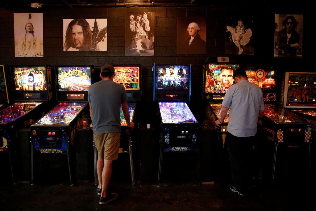 Jacob Boma (left) and Justin Hazlett play pinball at Craftcade Pinball Bar in Fort Worth.