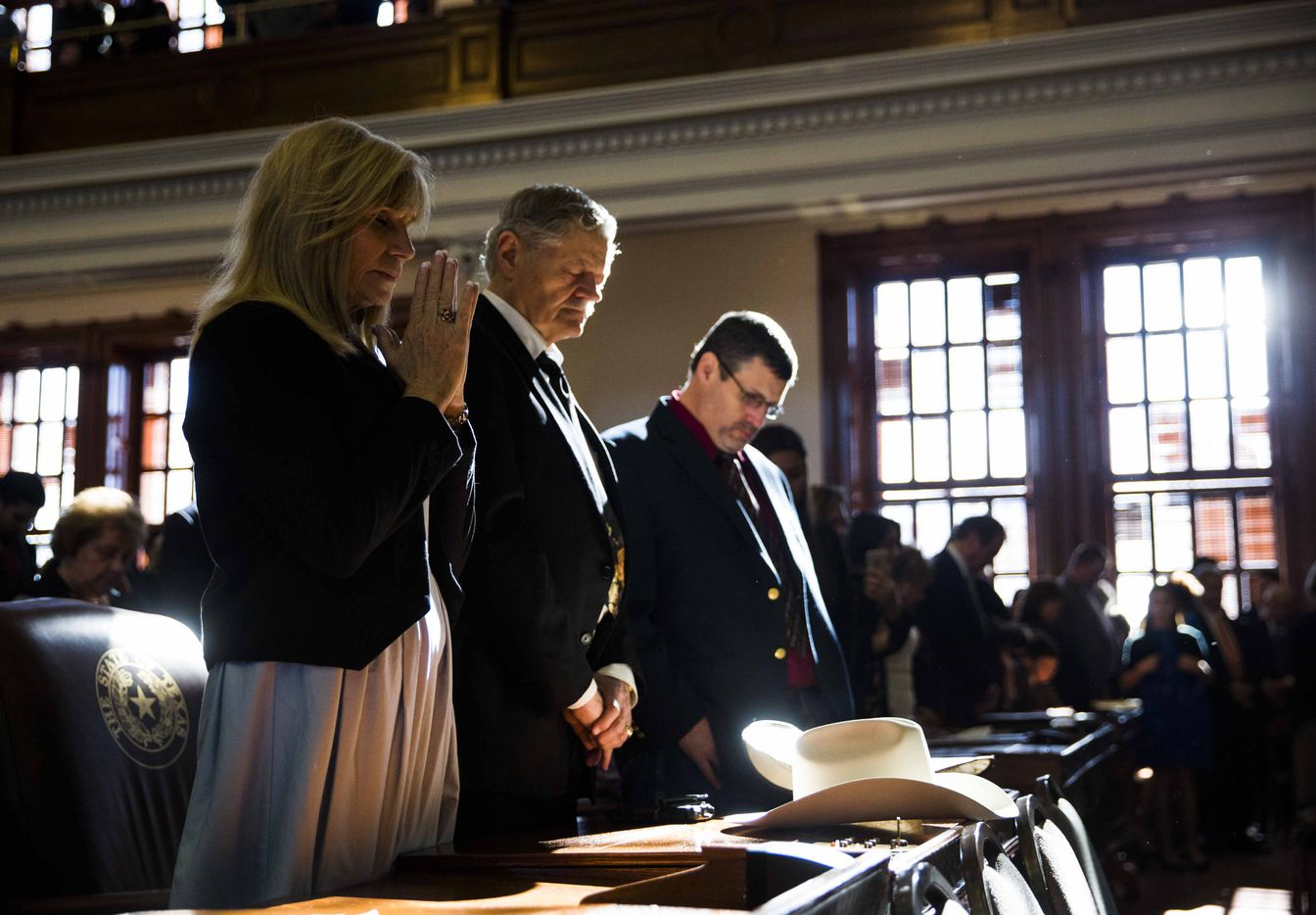 "Lyn Sullivan,  state Rep. Charles ""Doc"" Anderson and Thomas Schmitt, as well as other representatives and their families, pray during the benediction at the first day of the 85th Texas Legislative Session on Tuesday at the Texas State Capitol in Austin."