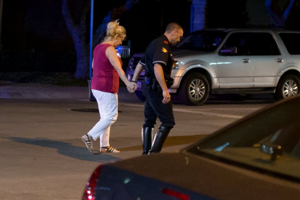 A police officer accompanies a family member of the injured officers to the car at Baylor Hospital Emergency Room on July 8, 2016 in Dallas, Texas. 11 Police officers shot, 4 dead, 1 person in custody after shots fired during downtown Dallas Black Lives Matters rally Thursday night. (Ting Shen/The Dallas Morning News)