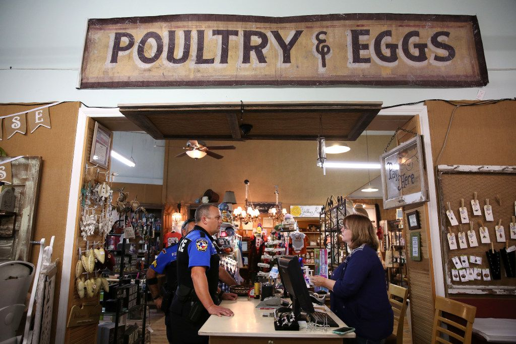 McKinney neighborhood police officer Randy Patton talks to Diana Daugherty, owner of 540 Mercantile, at her store in downtown McKinney. (Rose Baca/The Dallas Morning News)
