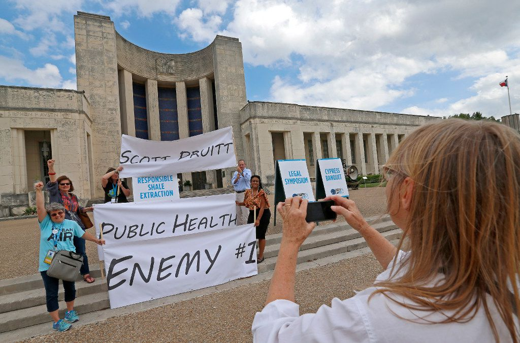 Valerie Walraven (right) takes a group photo of some of those protesting Pruitt's visit.