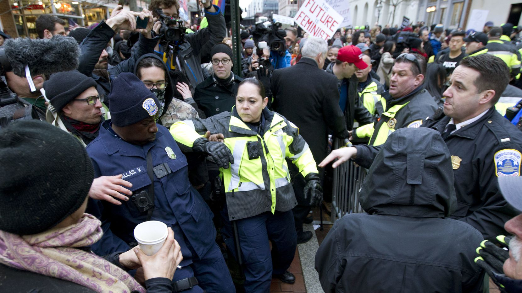 Police push back demonstrators attempting to block people entering a security checkpoint, Friday, Jan. 20, 2017, ahead of President-elect Donald Trump's inauguration in Washington. (AP Photo/Jose Luis Magana)