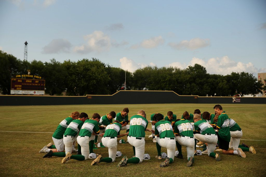 Santa Fe players join hands before the second game of the best-of-three series in the Class 5A Region III playoff high school baseball game between Santa Fe and Kingwood Park at Jim Kethan Field at Deer Park High School in Deer Park, TX Saturday May 19, 2018. On Friday morning, 10 people were killed and 13 were injured after a shooting at Santa Fe High School. The game was postponed to Saturday after it was scheduled for Friday. Dimitrios Pagourtzis was booked into the Galveston County Jail on capital murder charges.
