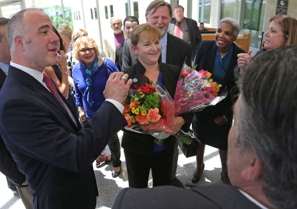 Former Judge Suzanne Wooten (center) was all smiles as she visited with her attorney Peter Schulte (left) and family and friends in the foyer of the Collin County Courthouse after her 2011 convictions were vacated.