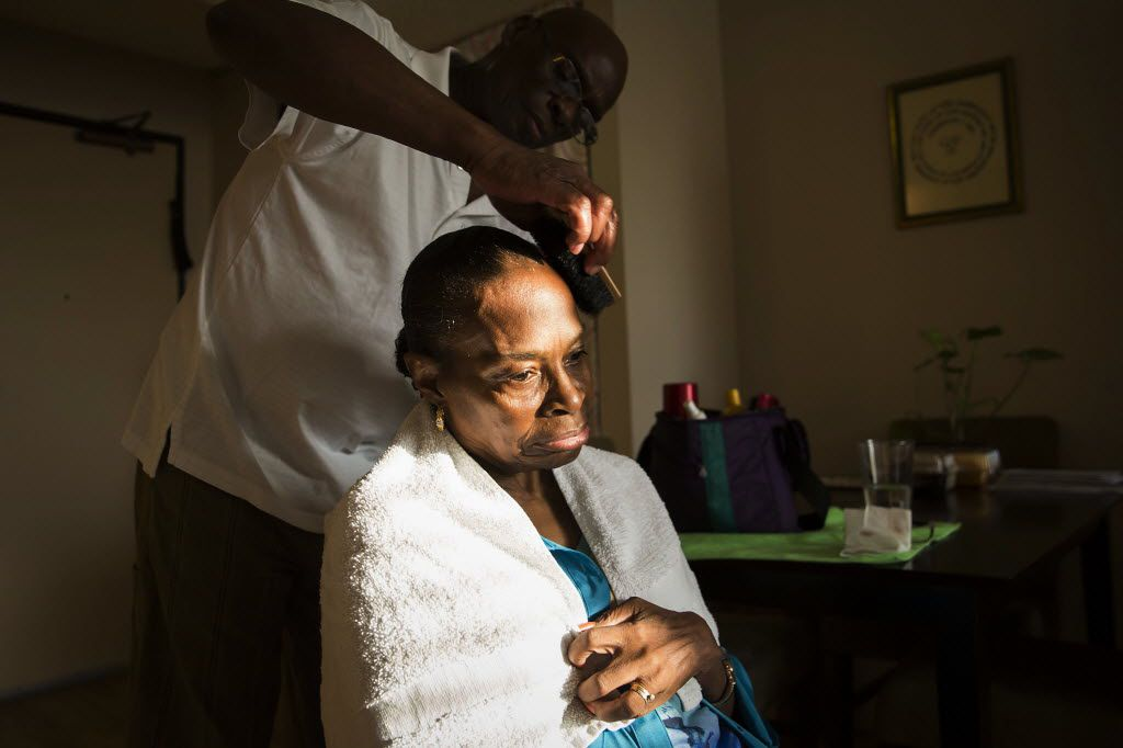 """Herbert fixes his wife's hair at their apartment in Dallas. """"He's a part of my life that I've always been missing: someone to love me, care for me and abide me,"""" Laura said."""