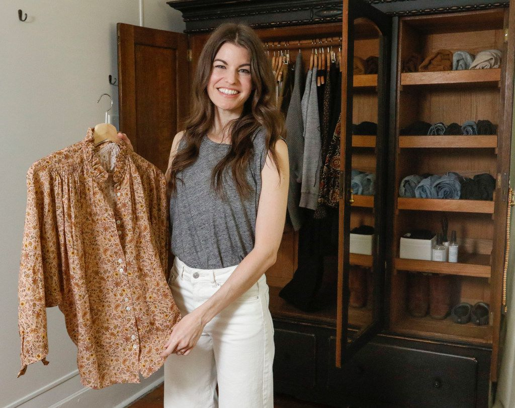 Caroline Rector holds a blouse she keeps with her spring and summer wardrobe in a  freestanding closet in her home.